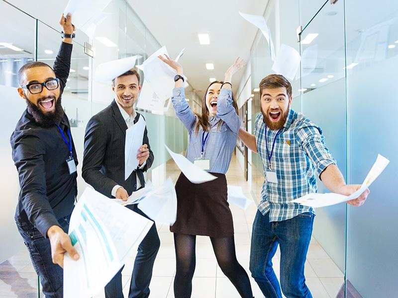 Jeunes employés heureux et effectuant un saut.