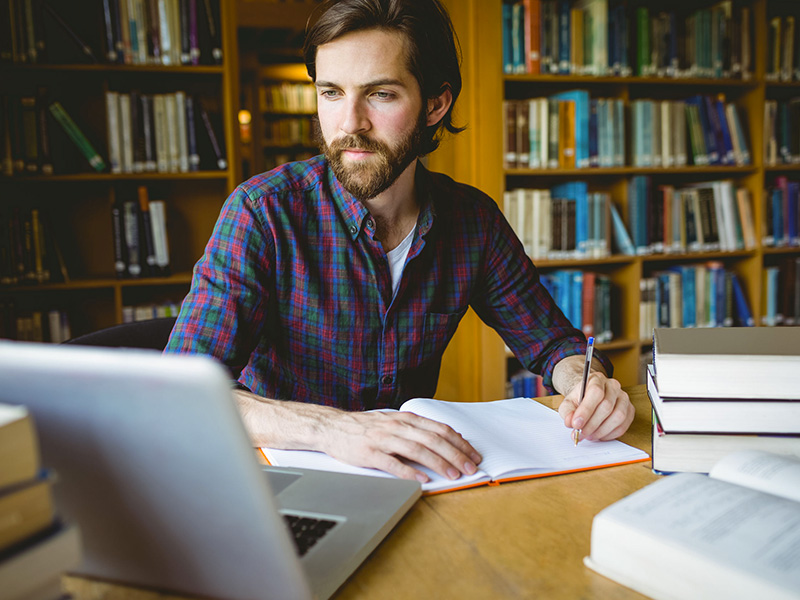 Jeune homme étudiant dans une bibliothèque.