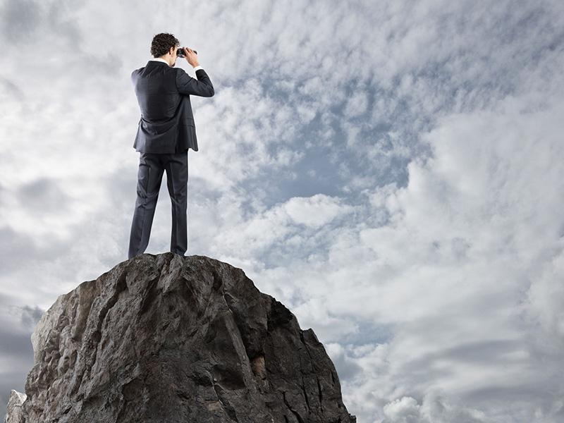 Homme d'affaires debout sur un pic rocheux, scrutant l'horizon avec des jumelles.