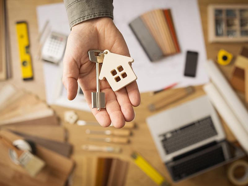 Main tenant une clé rattachée à un porte-clé en forme de maison.