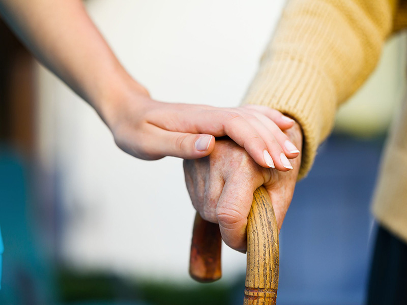 Personne âgée prenant appui sur un déambulatoire.