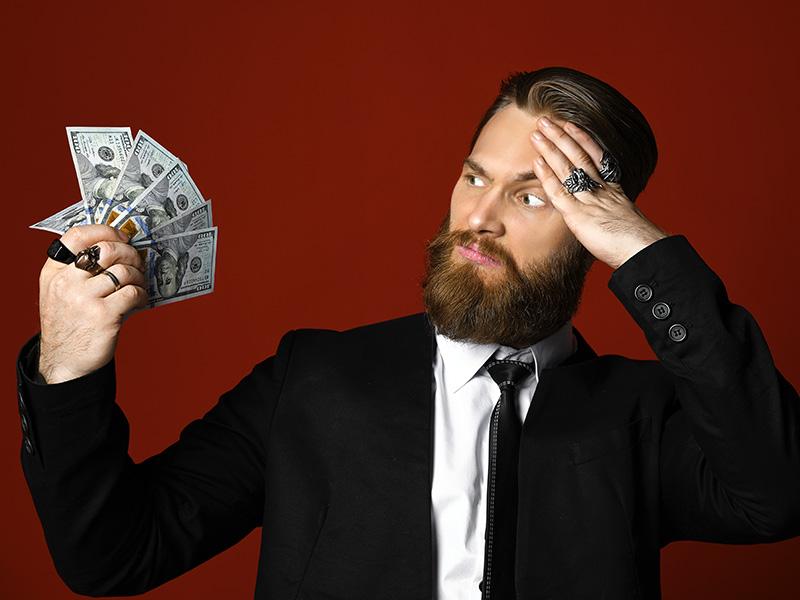 Jeune homme confus habillé en complet et tenant une liasse d'argent.