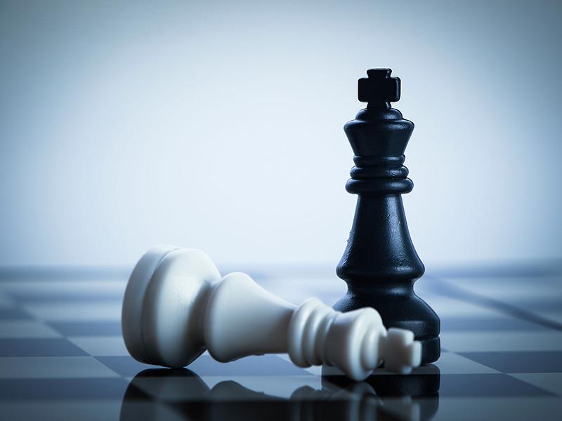 Deux pièces d'un jeu d'échec : le roi blanc renversé, le roi noir, debout.