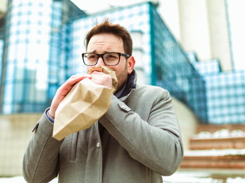 Homme qui respire dans un sac de papier.