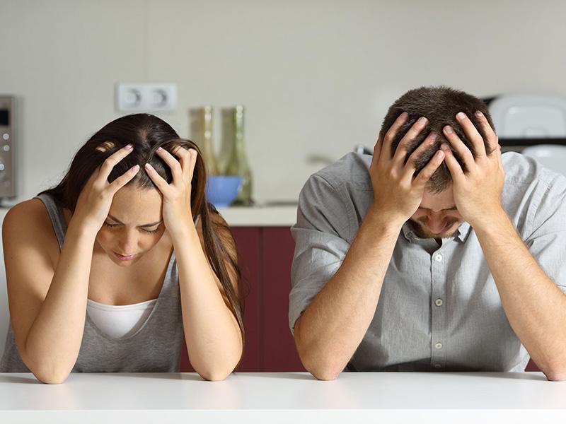 Jeune couple triste, les mains posées sur la tête.