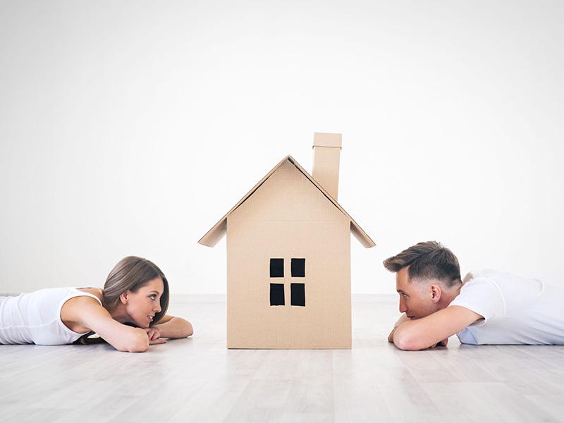 Jeune couple couché sur le ventre et se faisant face, avec, au centre, une maison de carton.