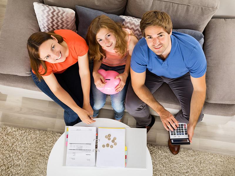 Jeune famille assise sur un sofa, dressant un budget avec une calculatrice.