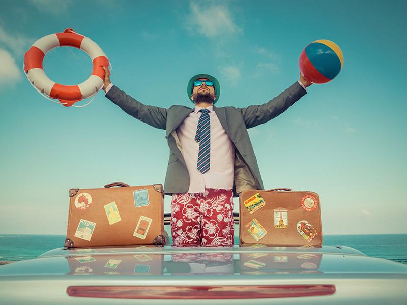 Homme d'affaires en vacances, avec une bouée de sauvetage et un ballon de plage dans les mains.