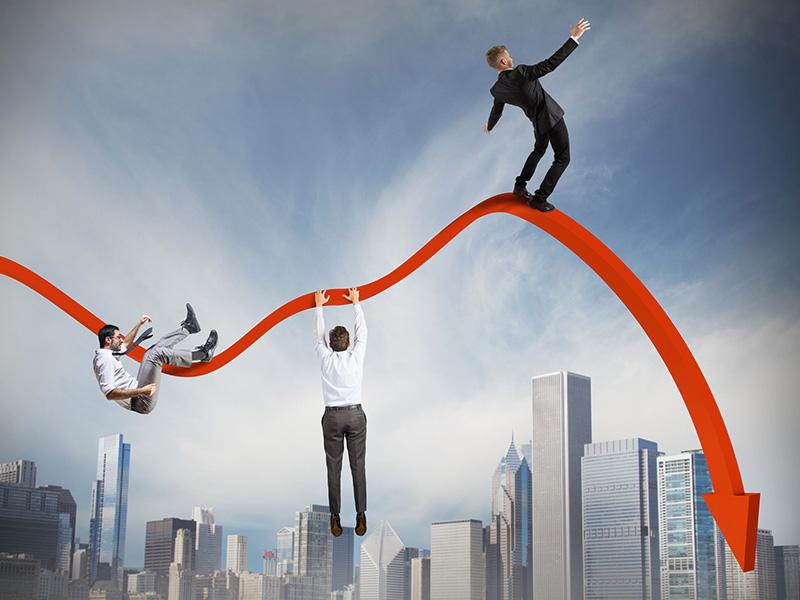 Hommes d'affaires se tenant en équilibre précaire sur une courbe de rendement affichant une forte baisse.
