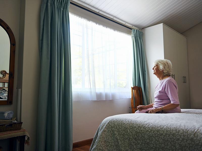 Femme âgée assise seule dans son lit.