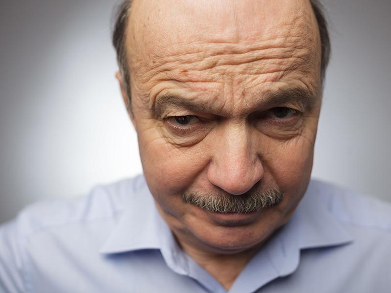 Homme d'âge mur fronçant les sourcils face à la caméra.