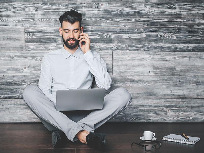 Jeune adulte assis par terre, un ordinateur portable sur ses jambes et parlant au cellulaire.