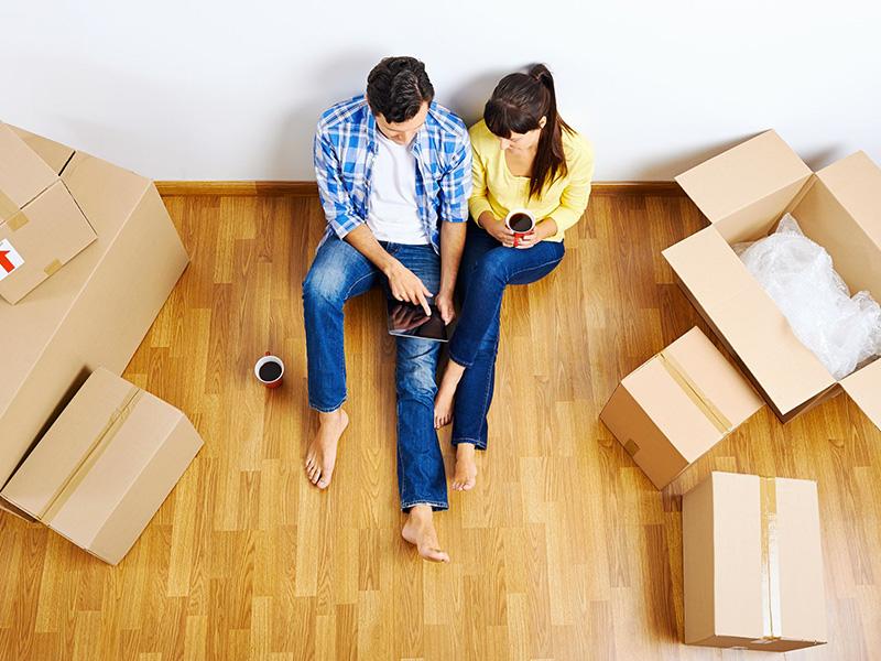 Jeune couple assis par terre, entouré de boîtes de carton.