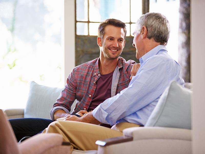 Un père retraité et son fils adulte discutent.