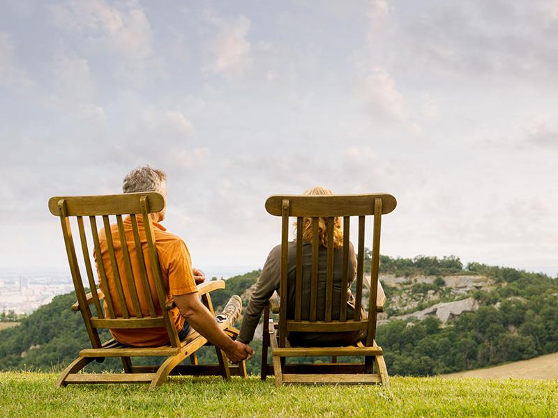 Couple de préretraités assis sur des chaises de bois dans la nature.