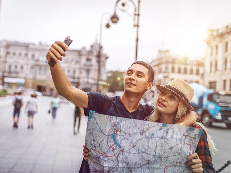 Jeune couple en voyage, tenant une carte routière et se prenant en selfie.