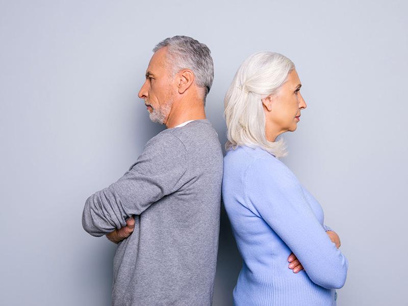 Couple dans la cinquantaine, dos à dos.