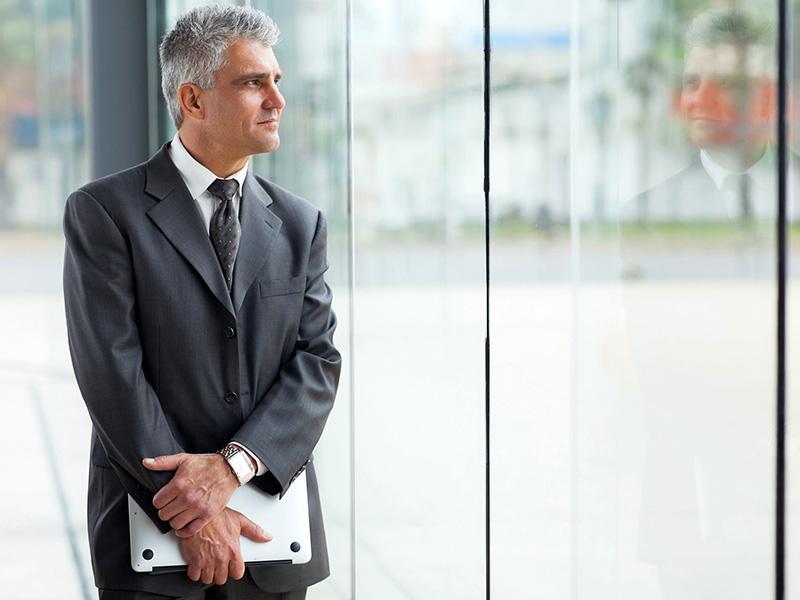 Homme d'affaires mature, regardant par la fenêtre d'un immeuble.
