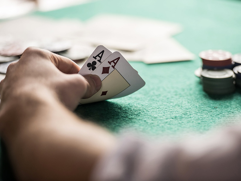 À une table de poker, gros plan d'une main tenant une paire d'as.