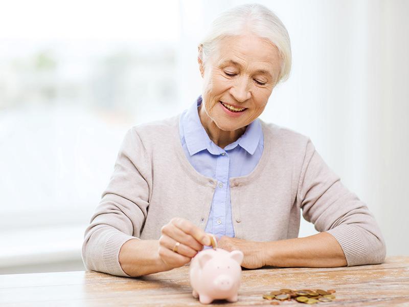Femme âgée déposant une pièce de monnaie dans une tirelire.