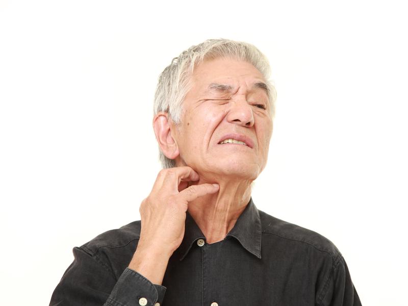 Homme qui se gratte le cou et a l'air inconfortable.