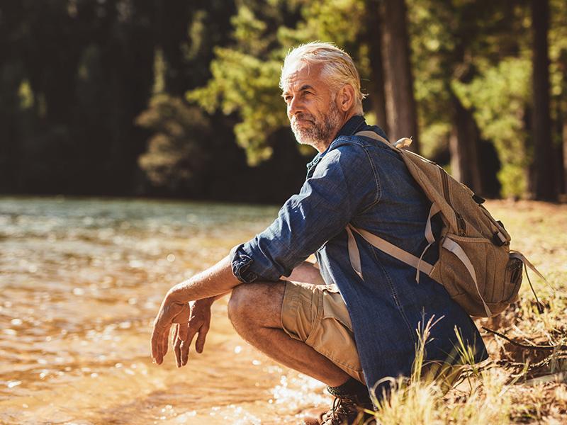 Homme retraité devant un lac.