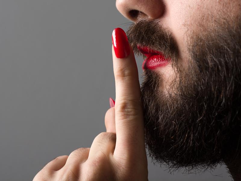 Homme portant du rouge à lèvres et du vernis à ongles faisant signe de rester silencieux.
