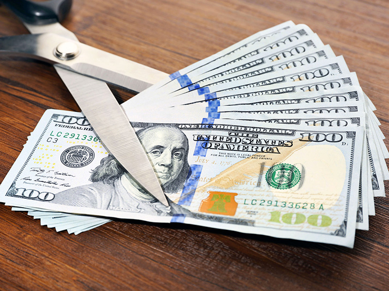 Couper une liasse de billets de banque avec des ciseaux.