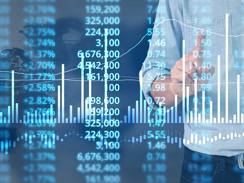 Un homme d'affaire devant un écran, évaluant le marché.