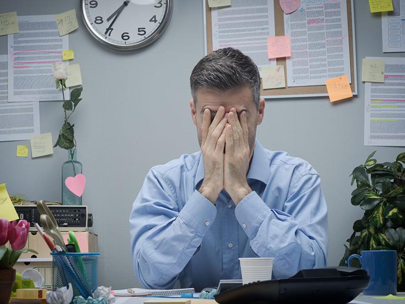 Employé de bureau se cachant le visage avec les mains.