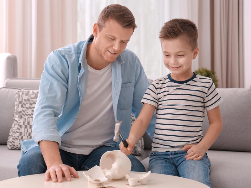 Un père et son fils assis sur un canapé face à une tirelire brisée. Le fils a un marteau dans les mains.