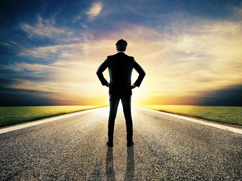 Un homme d'affaire debout sur une route, les mains sur les hanches face à un lever de soleil.