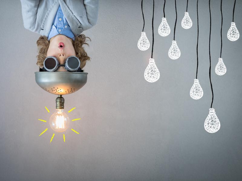 Photo d'un enfant avec une ampoule allumée attachée sur la tête, symbolisant une idée, l'innovation.