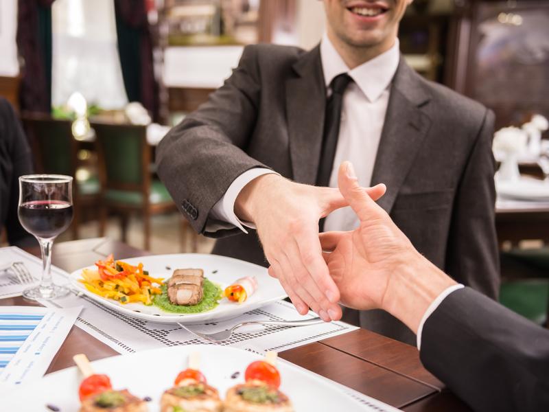 Hommes d'affaires qui se serrent la main au-dessus d'un repas au restaurant.