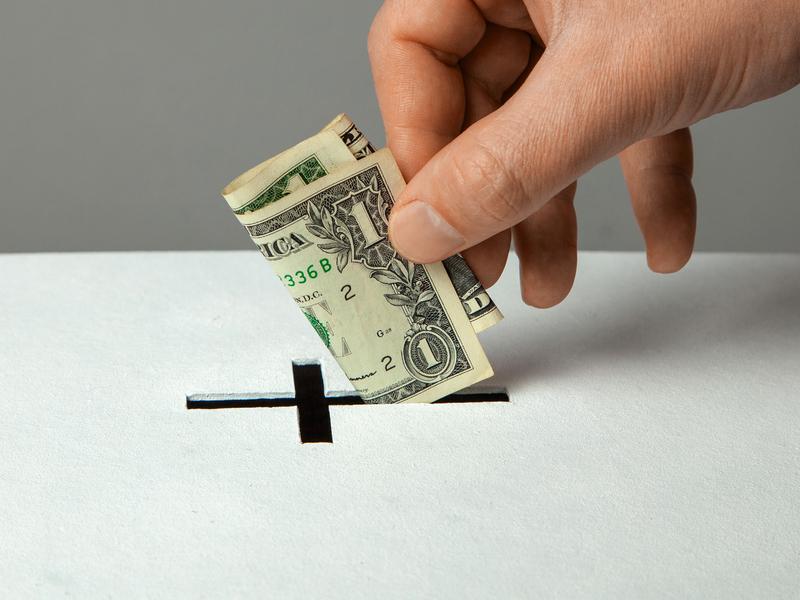 Main qui dépose un dollar dans une boîte dont l'ouverture est en forme de croix.