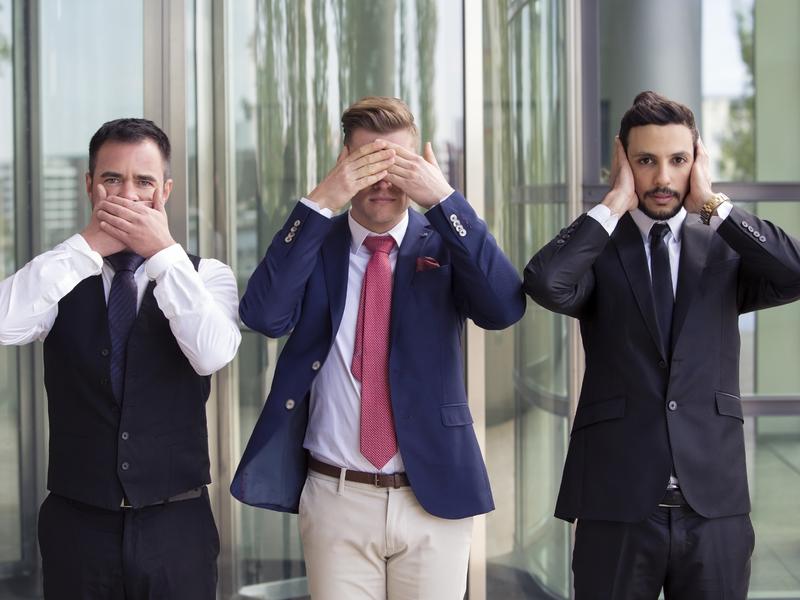 Trois hommes d'affaires illustrant les trois singes sages.