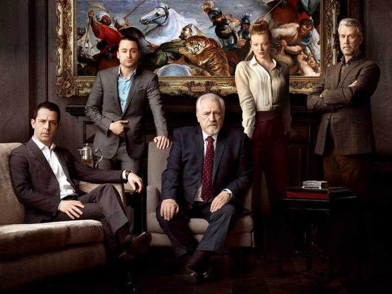 Une photo des 5 personnages de la série HBO Succession. 2 sont assis sur un divan, les trois autres sont debout derrière.