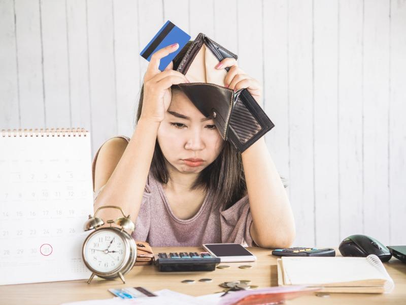 Femme ayant l'air découragée à la vue de son portefeuille vide, ses cartes de crédit et de la petite monnaie.