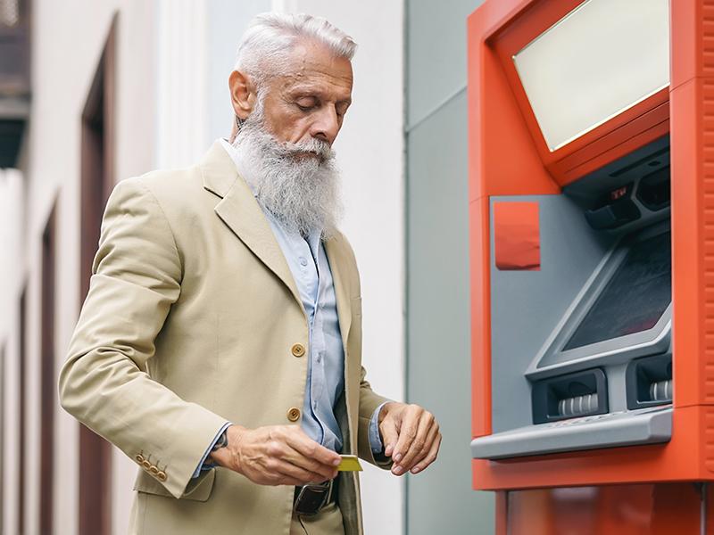 Homme âgé au guichet automatique