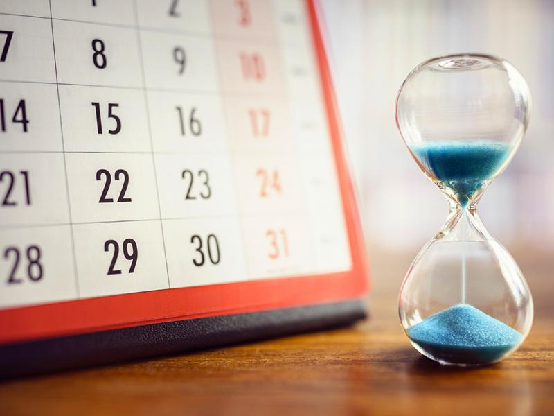 Un sablier posé à côté d'un calendrier.