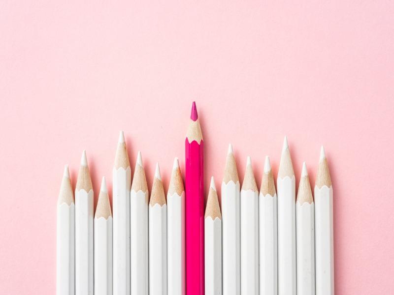 Rangée de crayons blancs avec un seul crayon rose qui se démarque.