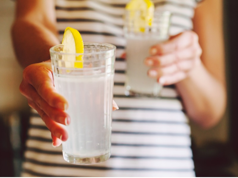 Femme qui tend un verre de limonade à quelqu'un d'autre.