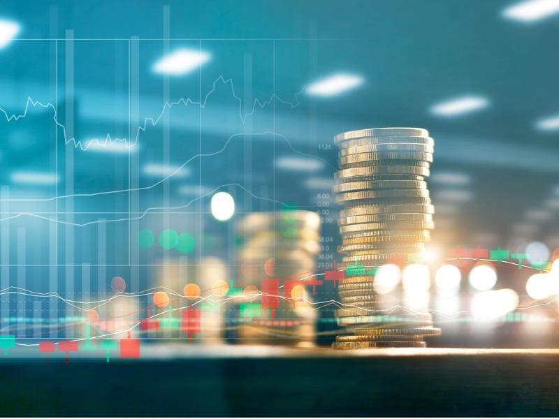 Piles de monnaie qui vont en croissant sur fond de graphique financier.