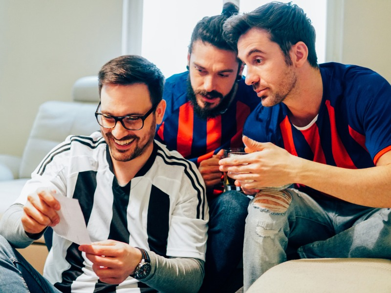 Trois hommes en maillot sportif dans un salon regardent un document de pari sportif.