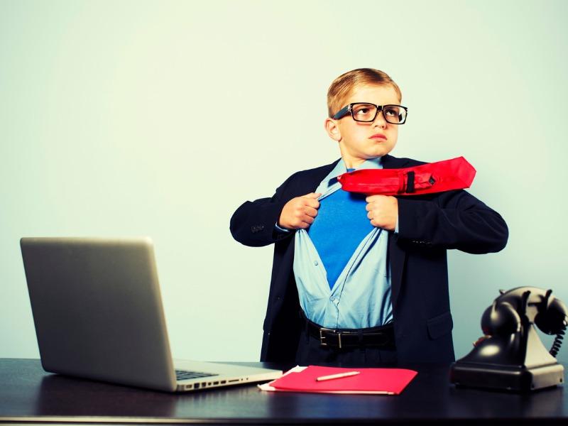 Enfant habillé en homme d'affaires qui ouvre sa chemise, révélant un costume de superhéros.