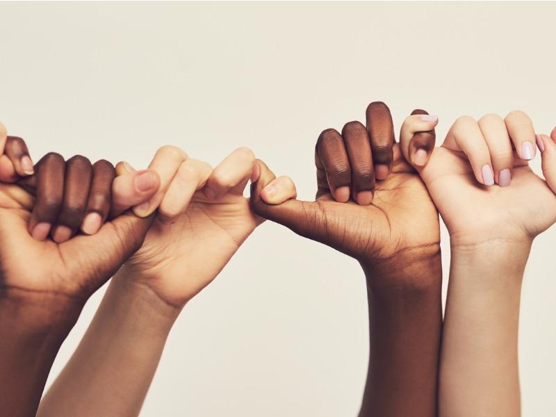 Mains de personnes de différentes origines qui se tiennent toutes par le petit doigt.