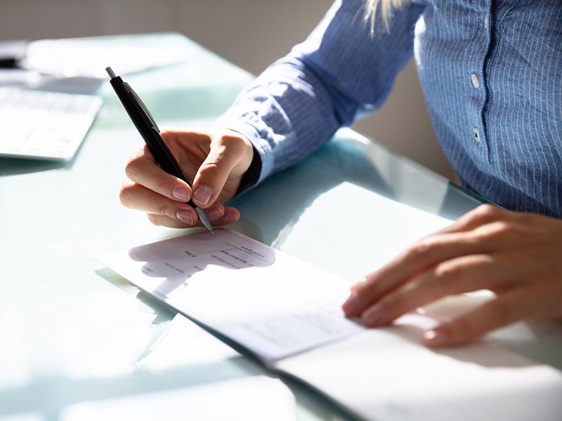 Femme d'affaires signe un chèque
