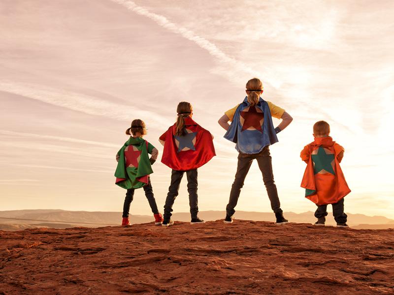 Un groupe de quatre jeunes enfants habillés en superhéros.