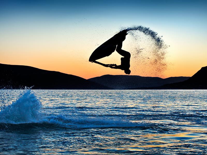 Conducteur de motomarine effectuant une acrobatie sur l'eau.