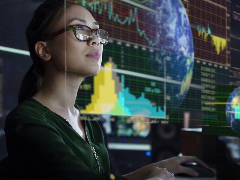 Femme qui regarde un écran où s'affiche graphiques et tableaux boursiers.